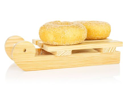 Group of two whole sweet golden mini cinnamon donut with wooden sledge isolated on white background
