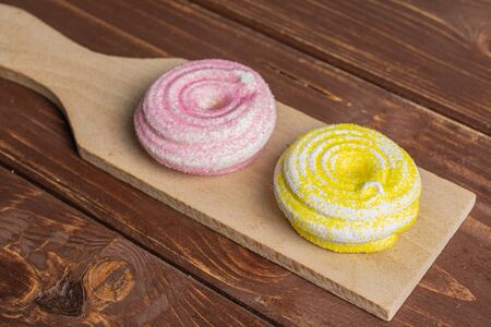 Group of two whole pink and yellow sweet meringue on small wooden cutting board on brown wood