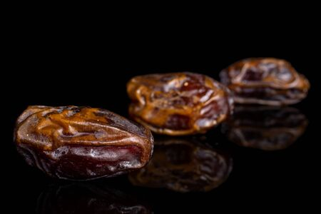 Group of three whole dry brown date fruit placed diagonally isolated on black glass Reklamní fotografie