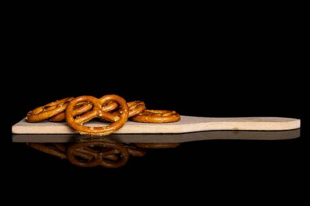 Group of six whole salty brown pretzel on small wooden cutting board isolated on black glass Reklamní fotografie