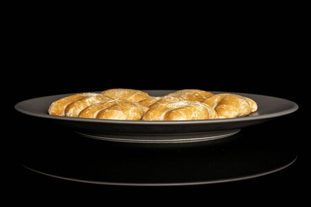 Group of seven whole sweet brown gingerbread on gray ceramic plate isolated on black glass