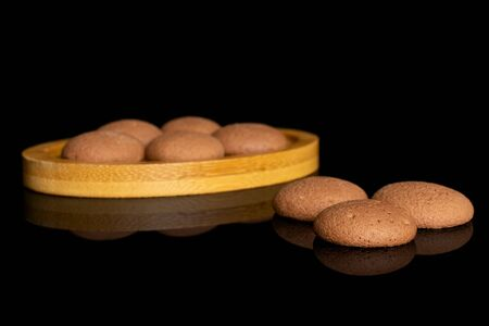 Group of eight whole sweet brown chocolate sponge biscuit on bamboo coaster isolated on black glass Reklamní fotografie