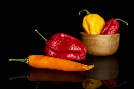 Group of four whole hot chili pepper in tiny wooden bowl isolated on black glass