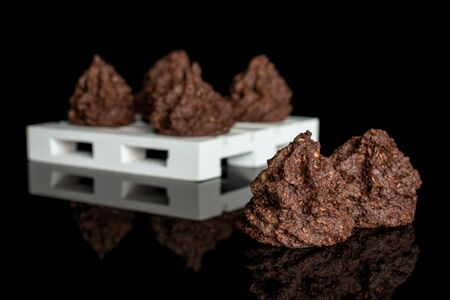 Group of six whole homemade brown coconut cocoa biscuit on white wooden pallet isolated on black glass
