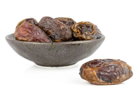 Group of six whole dry brown date fruit in dark ceramic bowl isolated on white background Reklamní fotografie