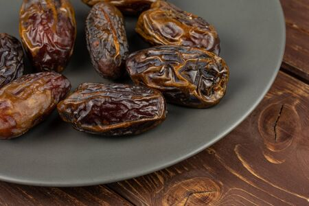 Lot of whole dry brown date fruit on gray ceramic plate on brown wood Reklamní fotografie