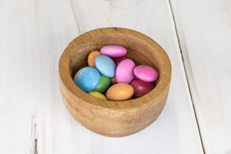 Lot of whole sweet colourful candy in bamboo bowl on white wood