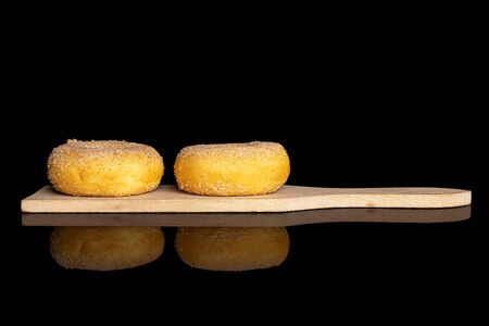 Group of two whole sweet golden mini cinnamon donut on small wooden cutting board isolated on black glass