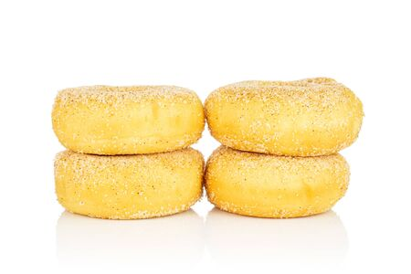 Group of four whole sweet golden mini cinnamon donut in two columns isolated on white background