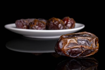 Group of five whole dry brown date fruit on white ceramic plate isolated on black glass