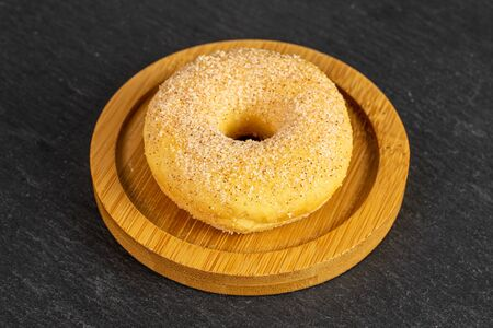 One whole sweet golden mini cinnamon donut on bamboo coaster on grey stone