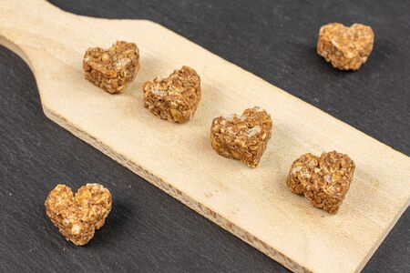 Group of six whole healthy brown cereal heart with cocoa on small wooden cutting board on grey stone