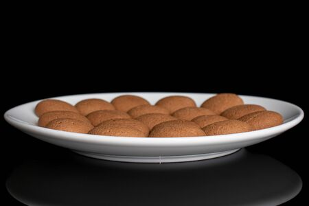 Lot of whole sweet brown chocolate sponge biscuit on white ceramic plate isolated on black glass