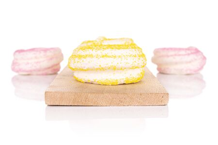 Group of four whole pink and yellow sweet meringue on small wooden cutting board isolated on white background Reklamní fotografie