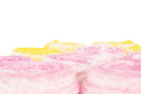 Lot of whole pink and yellow sweet meringue isolated on white background