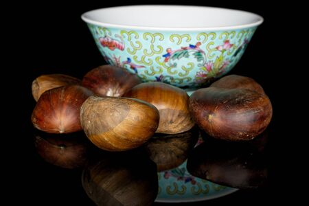 Group of six whole edible brown chestnut with blue chinese ceramic bowl isolated on black glass Reklamní fotografie