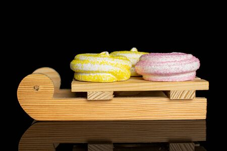 Group of three whole pink and yellow sweet meringue with wooden sledge isolated on black glass Reklamní fotografie