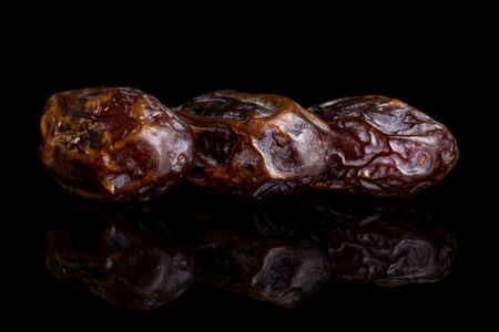 Group of three whole dry brown date fruit in row isolated on black glass Reklamní fotografie