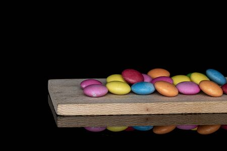 Lot of whole sweet colourful candy on wooden cutting board isolated on black glass