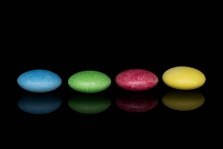 Group of four whole sweet colourful candy isolated on black glass Reklamní fotografie