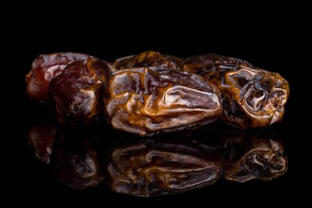 Lot of whole dry brown date fruit isolated on black glass Reklamní fotografie
