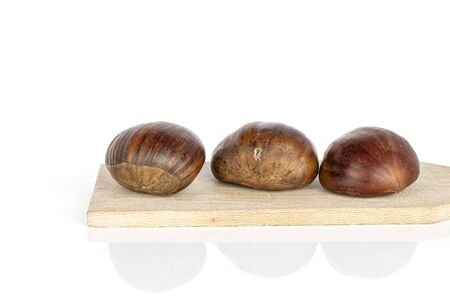 Group of three whole edible brown chestnut on wooden cutting board isolated on white background