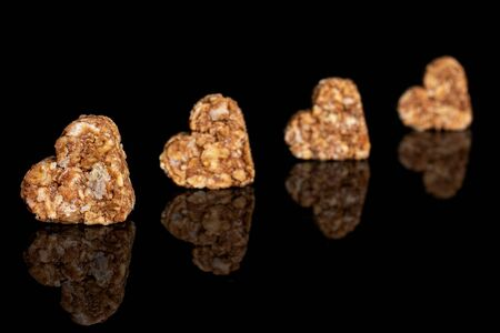 Group of four whole healthy brown cereal heart with cocoa isolated on black glass