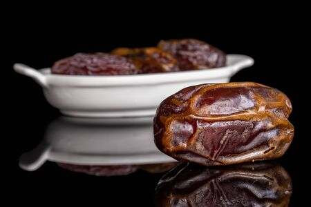 Group of four whole dry brown date fruit in white oval ceramic bowl isolated on black glass