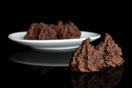 Group of six whole homemade brown coconut cocoa biscuit on white ceramic plate isolated on black glass