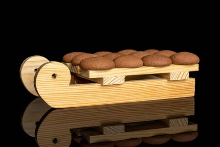 Lot of whole sweet brown chocolate sponge biscuit with wooden sledge isolated on black glass