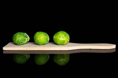 Group of three whole fresh green brussels sprout on small wooden cutting board isolated on black glass