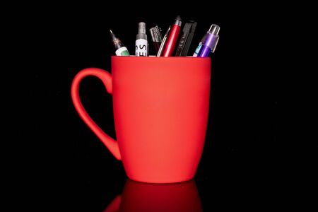 Lot of whole writing ballpoint pen with red ceramic cup isolated on black glass Zdjęcie Seryjne