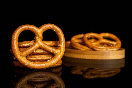 Group of eight whole salty brown pretzel on bamboo coaster isolated on black glass Reklamní fotografie - 140190495