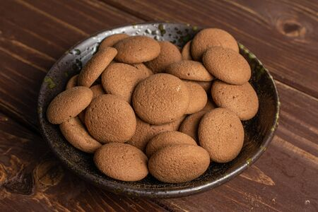 Lot of whole sweet brown chocolate sponge biscuit in dark ceramic bowl on brown wood Reklamní fotografie