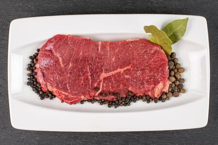 Beautiful raw beef sirloin with spices on white rectangular ceramic plate flatlay on grey stone