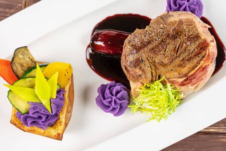 Beautiful beef steak with bacon and purple potato flowers and dark sauce on white rectangular ceramic plate flatlay on brown wood