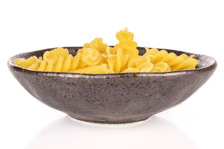 Lot of whole yellow pasta fusilli in glazed bowl isolated on white background