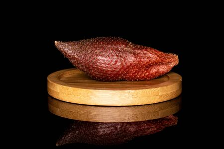 One whole exotic brown salak on round bamboo coaster isolated on black glass Stok Fotoğraf