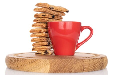 Lot of whole square puff cookie with raisins with red cup on coaster isolated on white