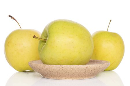 Group of three whole green delicious apple on plate isolated on white