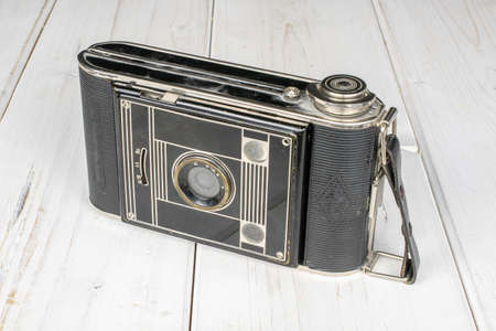One whole closed vintage camera on white wood