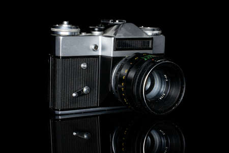 One whole old vintage camera isolated on black glass Editorial