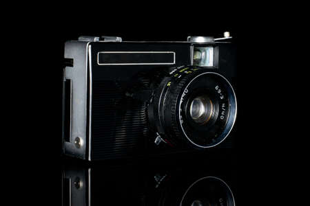 One whole dark vintage camera isolated on black glass