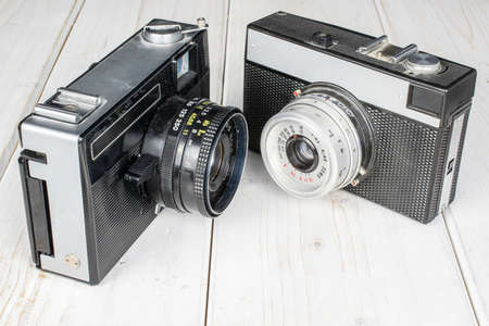 Group of two whole vintage camera on white wood Editorial