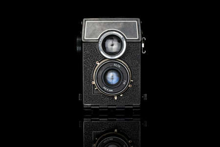 One whole vintage camera isolated on black glass