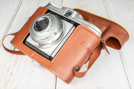 One whole vintage camera in brown case on white wood