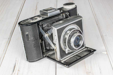 One whole vintage camera on white wood Editorial