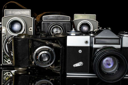 Group of five whole vintage camera isolated on black glass Editorial