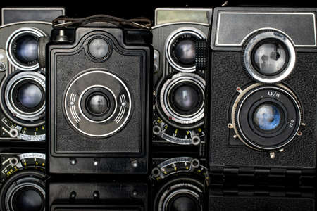 Group of four whole vintage camera isolated on black glass