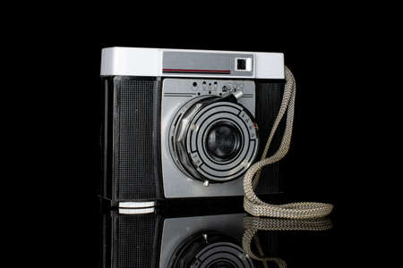 One whole vintage camera one lens isolated on black glass Editorial